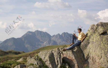 坐在岩石上休息的男人图片